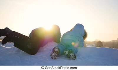 children playing on a snowy hill. Winter landscape. Sunset time