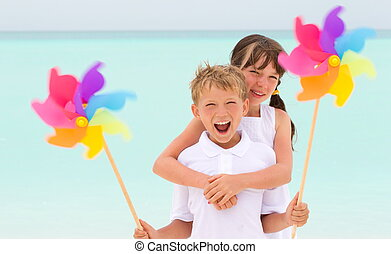 : Happy young brother and sister playing with colorful windmill toys on beach, sea in background.