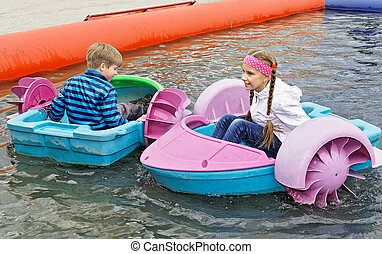 Children playing on toy boats