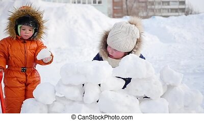 children playing outdoors in winter. The child builds a wall of snow stones
