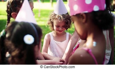 Children playing outdoors on birthday party in garden in ...