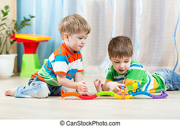 children playing rail road toy in playroom
