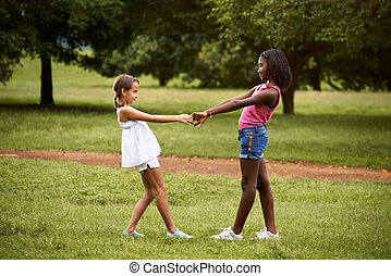 Children playing ring around the rosie in park - Two ...