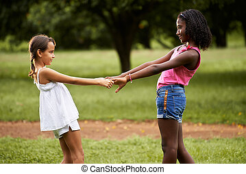 Children playing ring around the rosie in park
