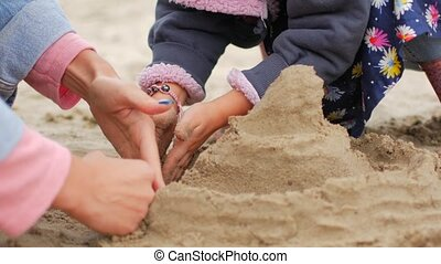 Children playing sand on the beach. Little girl builds sand...