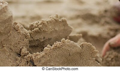 Children playing sand on the beach. Little girl builds sand castle by himself on the beach.