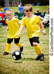 Children playing soccer in organized youth game
