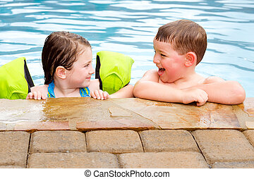 Children playing together laughing and smiling while swimming in pool