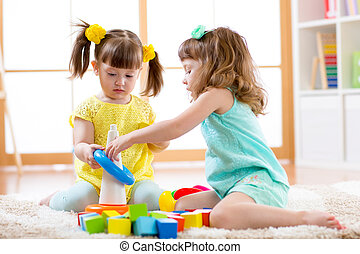 Children playing together. Toddler kid and baby play with blocks. Educational toys for preschool and kindergarten child. Little girls build pyramid toys at home or daycare.