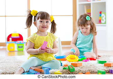 Children playing together. Toddler kids play with blocks. Educational toys for preschool and kindergarten child. Little girls build pyramid toys at home or daycare.