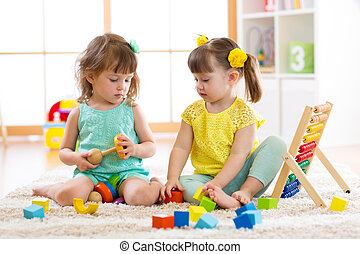 Children playing together with building blocks. Educational toys for preschool and kindergarten kids. Little girls build toys at home or daycare.