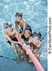 Children playing tug of war in pool