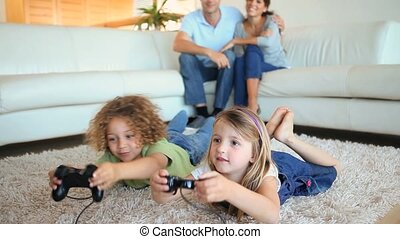 Children playing video games to the on a carpet