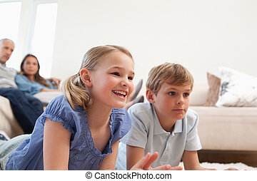 Children playing video games while their parents are watching