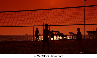 Children playing volleyball on the beach at sunset
