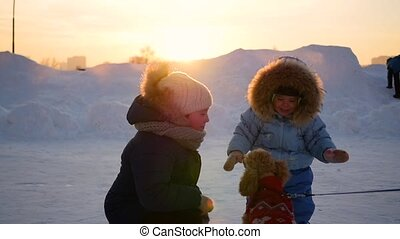 children playing with a dog in winter at sunset