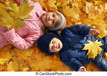 Children playing with autumn fallen leaves in the park