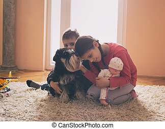 Children playing with dog on carpet
