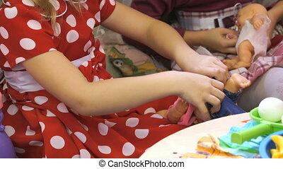 Children playing with dolls in kindergarten. Close up