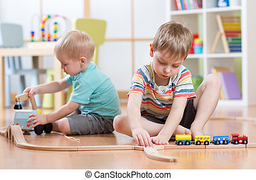 Children boys playing with educational toys and building rail road