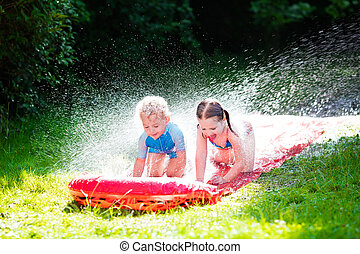 Children playing with garden water slide