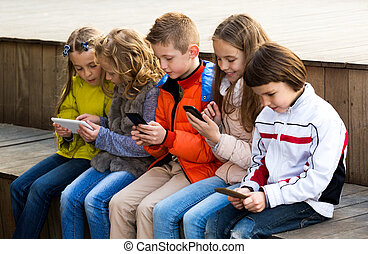 Children playing with mobile phones - Outdoor portrait of ...