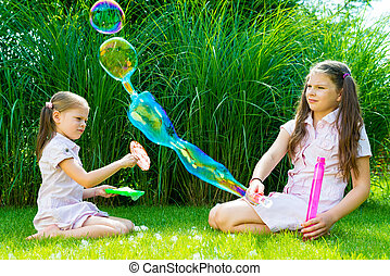 Children playing with soap bubble wand in the park on a sunny summer day