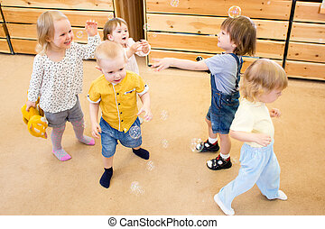 Children playing with soap bubbles in kindergarten