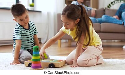 children playing with toys and parents at home - childhood,...