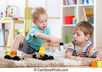 Children playing with wooden car at home or daycare. Educational toys for preschool and kindergarten kid.