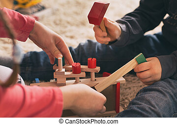 Children playing with wooden toys on floor
