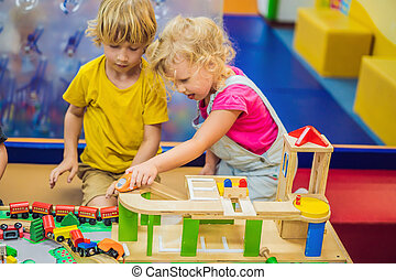 Children playing with wooden train. Toddler kid and baby play with blocks, trains and cars. Educational toys for preschool and kindergarten child. Boy and girl build toy railroad at home or daycare
