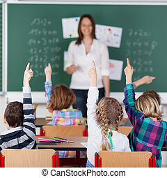Portrait of children raised their hands in the classroom