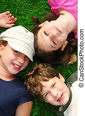 Children - Portrait of three young children lying on grass...