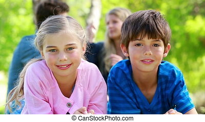Children posing while parents are talking in background