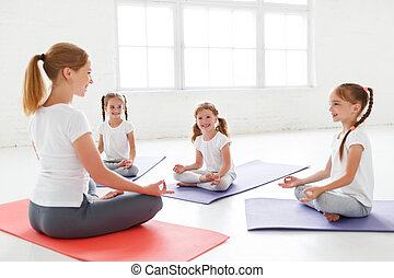 children practicing engaged in gymnastics and yoga with teacher