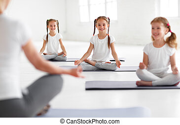 children practicing yoga in a lotus pose with teacher