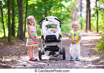 Boy and girl walk in sunny summer park pushing stroller with newborn sibling. Brother and sister playing with baby outdoors. Family with three kids walking in a forest. Group of little children.