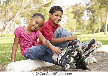 Children Putting On In Line Skates In Park