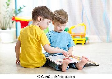 children read a book sitting on floor