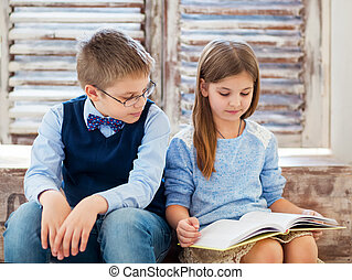 Children reading book in living room