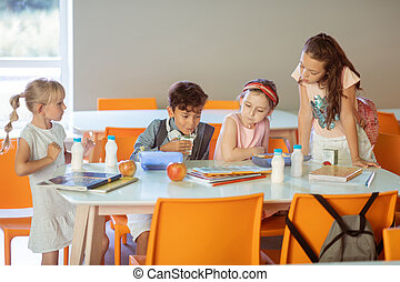 Children repeating some material and eating lunch in canteen