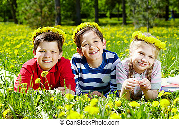 Children resting - Three children with dandelion wreaths...