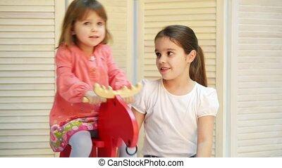 Children ride on toy horse