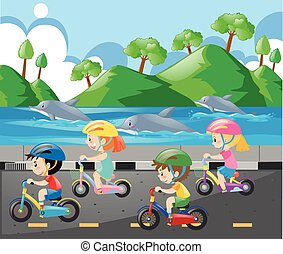 Children riding bike along the ocean