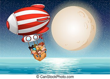 Children riding in the hot air balloon at night