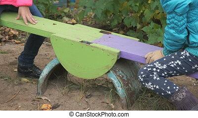 Children riding on swing sitting together - Unknown children...