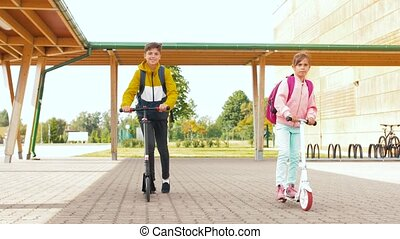 children riding scooters at school yard - education, ...