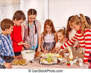 Children rolling dough in kitchen.