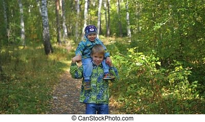 children run along the path in Park in autumn